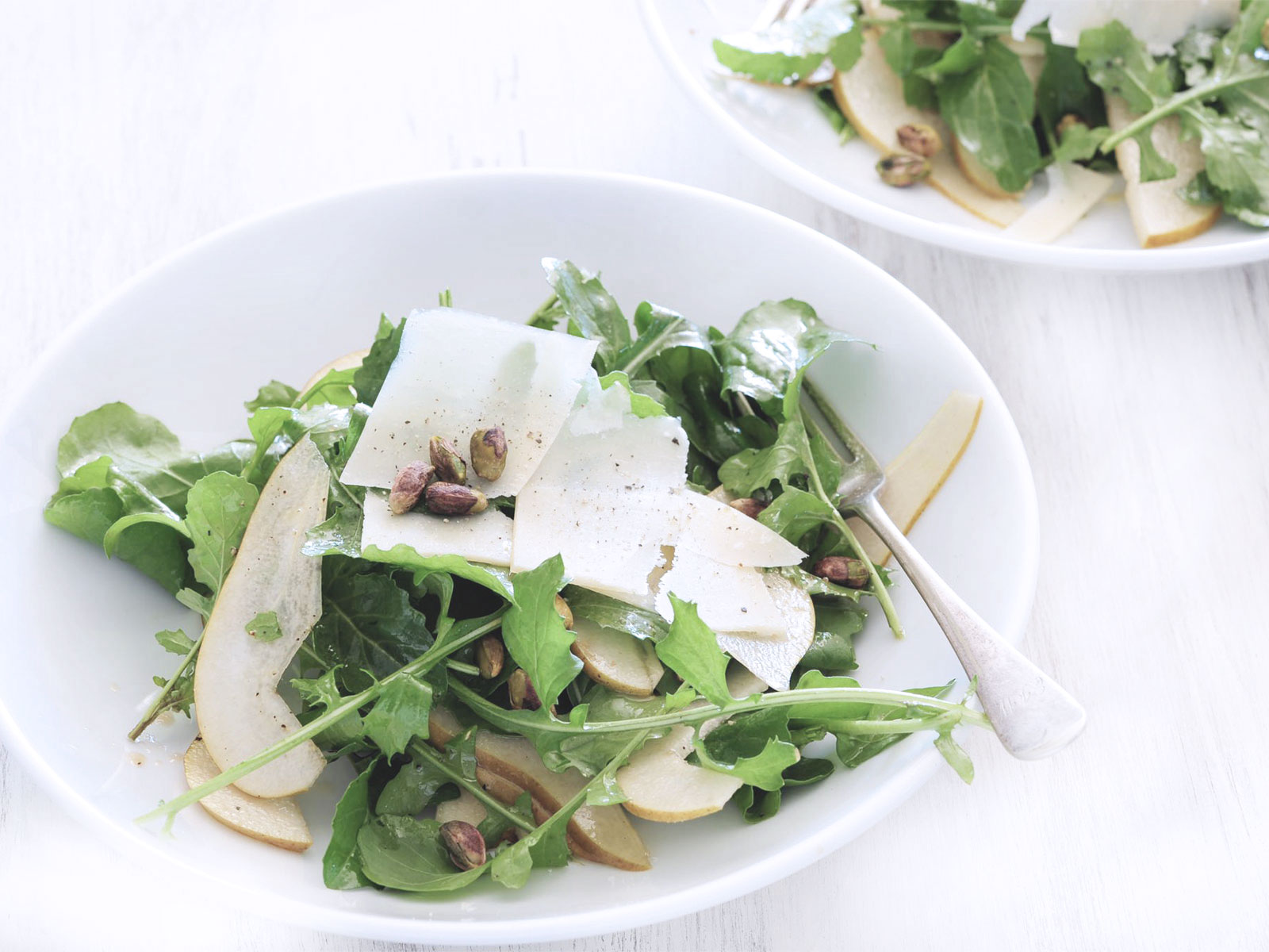 Finely sliced raw artichoke hearts and rocket lettuce topped with parmesan cheese